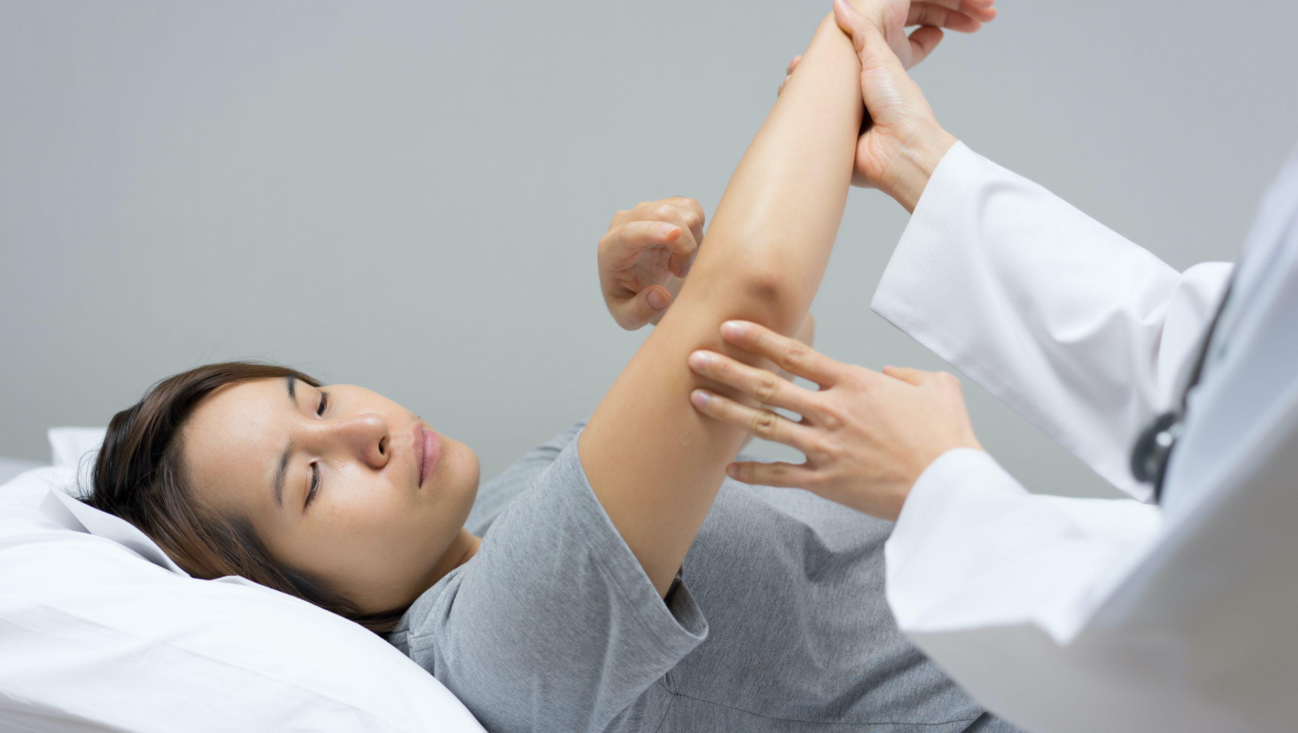Doctor examining patient elbow